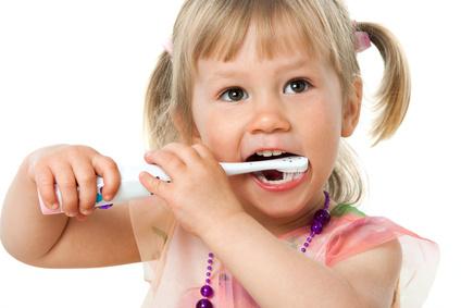 Close up portrait of cute girl brushing teeth.