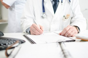 Doctor signing a medical report